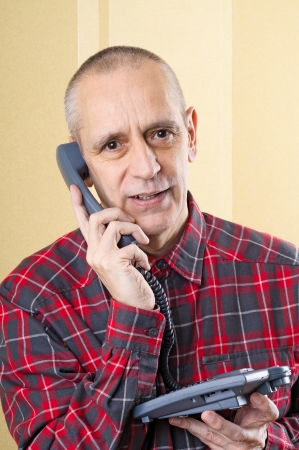 neighbourly: Amiable man smiling while speaking on phone Stock Photo