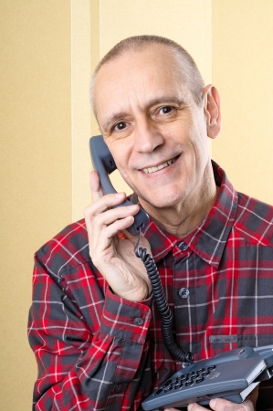 neighbourly: Cheerful man smiling and speaking on phone Stock Photo