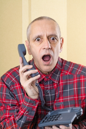 A senior man surprised by an incredible new on home phone photo