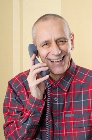 neighbourly: Happy man laughing and speaking with a friend on phone