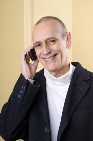 neighbourly: Smiling businessman speaking on mobile phone Stock Photo