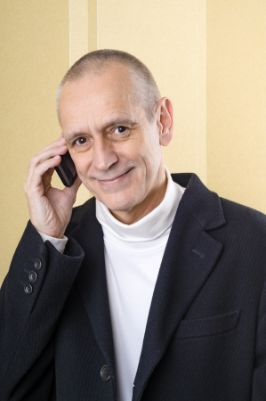 neighbourly: Handsome businessman with a black coat, smiling and speaking on mobile phone