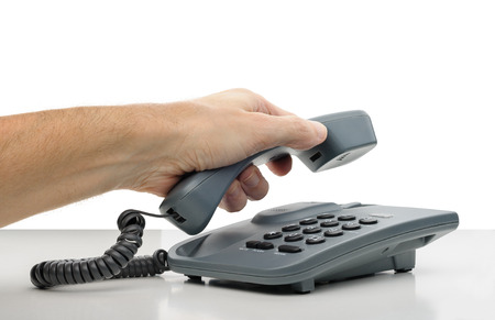 A man s hand hanging the phone receiver photo