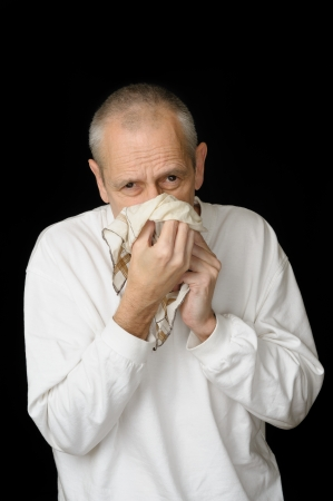 A sick man with cold holding an handkerchief in hands and blowing his nose photo