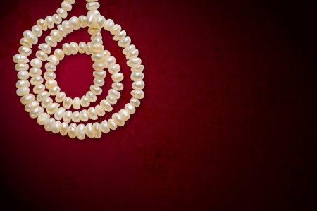 bordeau: Natural pearls necklace in spiral on a red background, with space for copy text