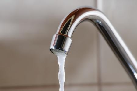 Horizontale afbeelding van een kraan met water langzaam stroomt in een periode van schaarste