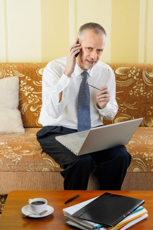 businessman working at his computer: An handsome worried senior businessman working with computer at home, calling to a customer with his mobile phone and ready to drink a hot cup of black coffee