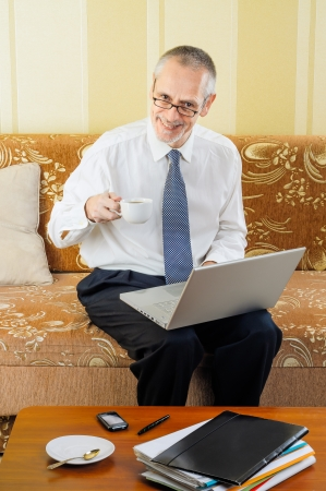 An handsome senior businessman working with computer at home, holding spectacles in his hand and ready to drink a hot cup of black coffee