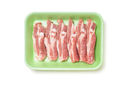 Pork ribs in a green foam tray, isolated on white background 스톡 콘텐츠