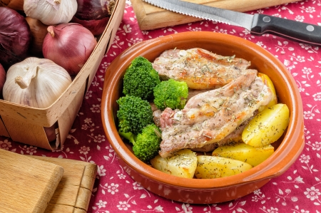Preparation of pork ribs with herbs, spices, broccoli and potatoes in a terracotta dish photo