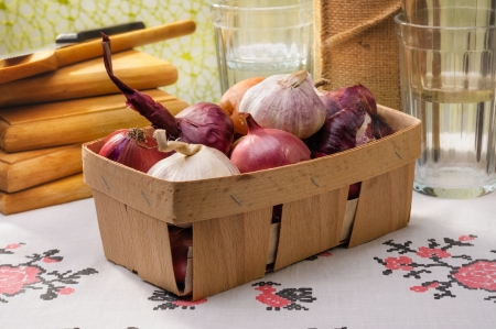 close up of onions in a basket: Close-up of a little wooden crate containing red and yellow onions and garlic, with cutting board, knife and glasses in the background Stock Photo