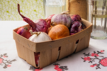 close up of onions in a basket: Close-up of a little wooden crate containing red and yellow onions and garlic, on a tablecloth with glasses in the background