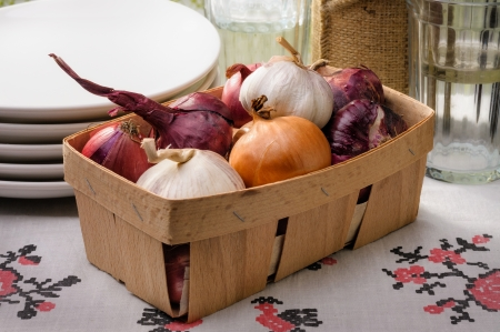 close up of onions in a basket: Close-up of a little wooden crate containing red and yellow onions and garlic, with white ceramic plates and glasses in the background Stock Photo