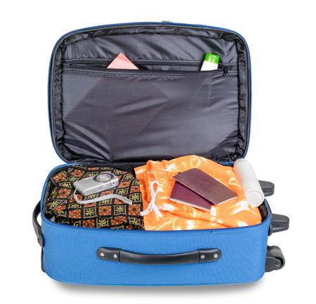 Open blauwe koffer klaar voor een vakantiereis, met digitale fotocamera en paspoorten, geïsoleerd op witte achtergrond