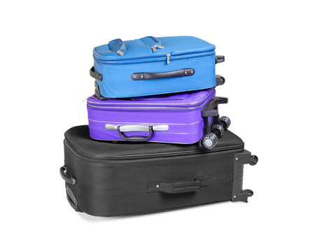 Three full and closed suitcases, black, blue and violet, ready for the trip, isolated on white background photo