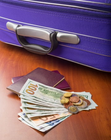 Dollars, Euros and Passports with a violet suitcase, ready for a business or holiday travel abroad. photo