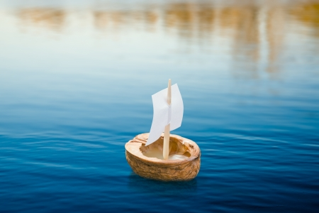 A walnut shell with a sail, floating on the blue lake