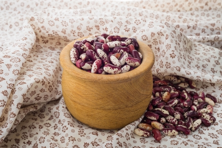 roman beans: Red Cannellini beans in a wooden bowl on a flourish tablecloth