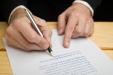 A businessman writing with a fountain pen on a white paper set on a wooded deck photo