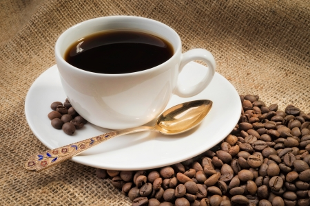 A warm cup of coffee with coffee beans photo