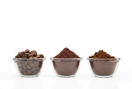 Koffiebonen, gemalen koffie en oploskoffie, in kleine glazen kopjes op een schone witte