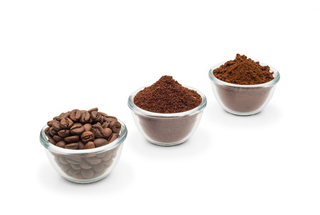 Coffee beans, ground coffee and instant coffee, in little glass cups on a clean white