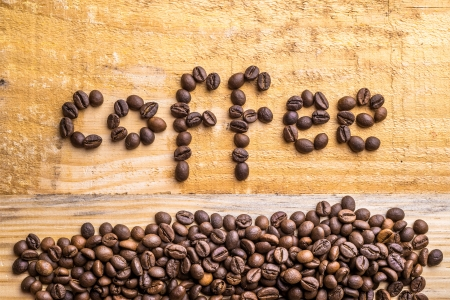 noun: Light wood texture with coffee beans writing the word coffee