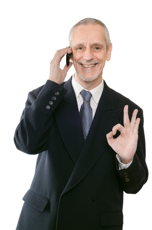 neighborly: An amiable businessman smiling on mobile phone and showing the okay sign with the hand Stock Photo