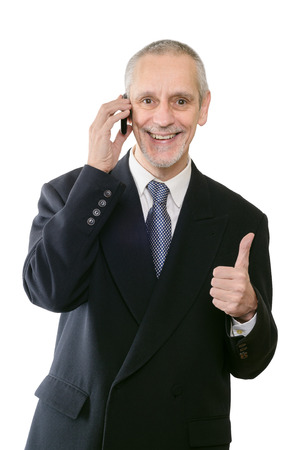 neighbourly: An amiable businessman smiling on mobile phone, with thumb up Stock Photo