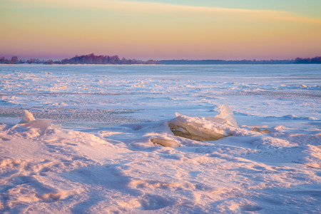 Icy Dnieper River with pink and blue reflections during the sunrise hour photo