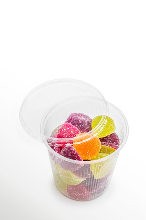 Colorful fruit jelly in open foam jar, on white  photo