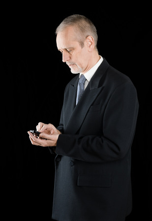 neighborly: Senior businessman in black suit writing sms or dialing a number on his mobile phone, on black background Stock Photo