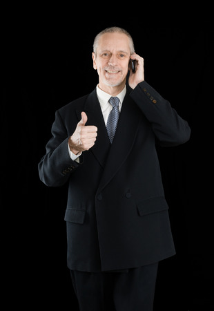 An amiable businessman wearing a black suit  smiling and speaking on mobile phone, with thumb up, on black background