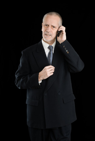 preoccupied: Happy businessman wearing a black suit, worried  and preoccupied on mobile phone, on black background