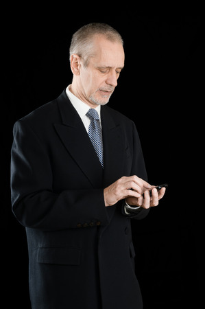 neighbourly: Senior businessman in black suit writing sms or dialing a number on his mobile phone, on black background Stock Photo