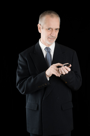 neighbourly: Senior businessman in black suit, writing sms or dialing a number on his mobile phone, on black background