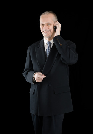 neighbourly: An agreeable businessman wearing a black suit smiling while speaking on mobile phone, on black background