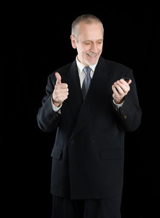 neighbourly: An amiable businessman wearing a black suit  smiling and reading on mobile phone, with thumb up, on black background