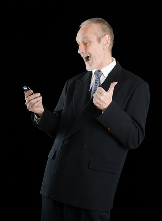 Happy businessman wearing a black suit, smiling and reading sms on mobile phone, with thumb up, on black background photo