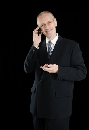 neighborly: An agreeable businessman wearing a black suit smiling while speaking on mobile phone, on black background