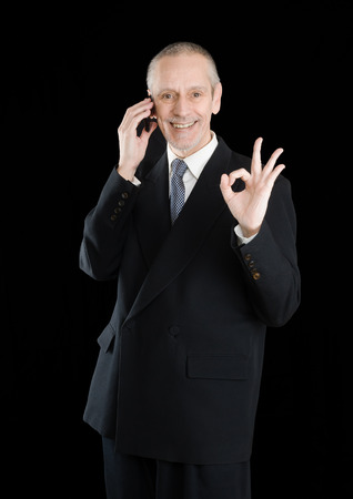 neighbourly: An amiable businessman in black suit, smiling on mobile phone and showing the okay sign with the hand, on black background Stock Photo