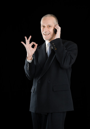 amiable: An amiable businessman in black suit, smiling on mobile phone and showing the okay sign with the hand, on black background Stock Photo