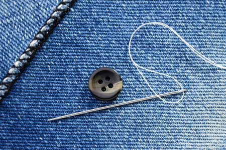 Sewing a button on  blue jeans fabric photo