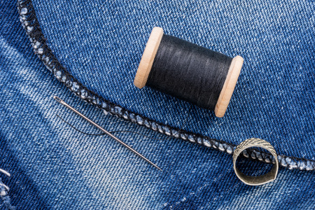 A roll of black thread and a needle on a piece of blue jeans denim photo