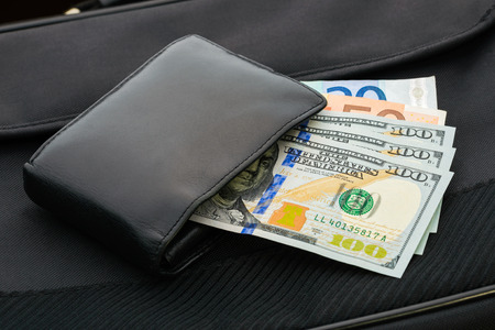 A black leather wallet with Dollar  and Euro banknotes photo