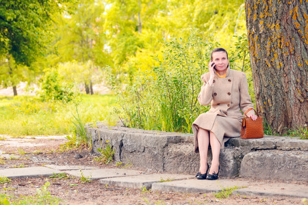 topknot: Elegant businesswoman sitting on a stone wall during a sunny spring day, and phoning to a customer Stock Photo