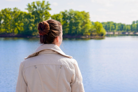 woman back: A woman with a chignon looking at the river during a nice sunny spring morning