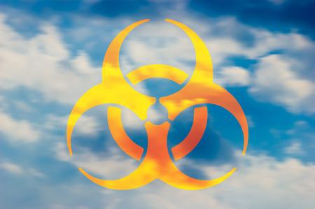 riesgo biologico: Símbolo de riesgo biológico en el cielo con nubes