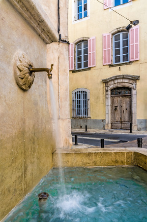 A fountain flowing fresh water in the town of Brignoles in Provence, south of France photo
