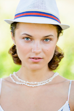 backlite: Portrait of a young woman with a white hat, smiling in the park, with summer back light and trees in the background